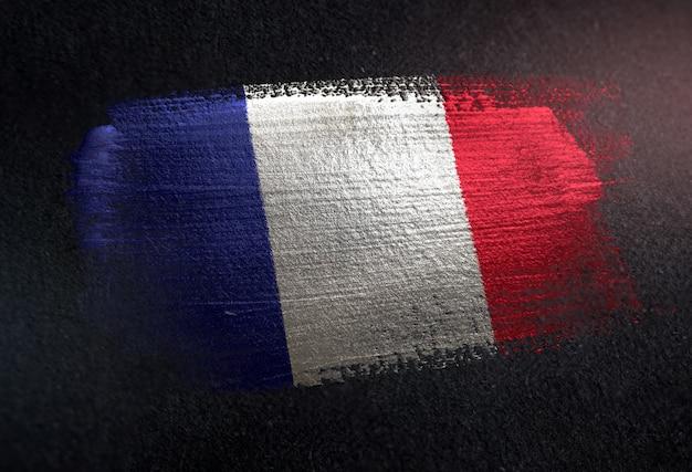 Frankreich-flagge gemacht von der metallischen bürsten-farbe auf dunkler wand des schmutzes
