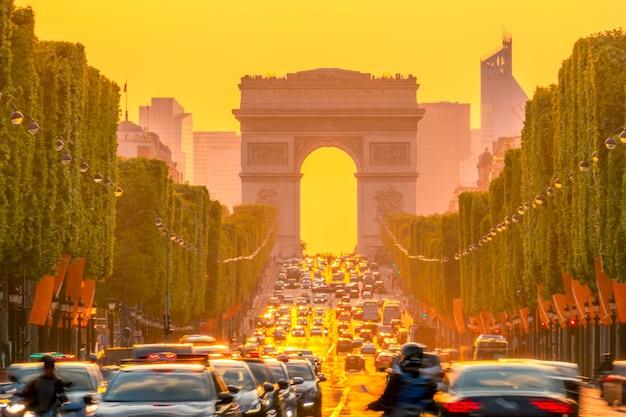 Frankreich. paris. dichter verkehr auf den champs elysees. triumphbogen auf einem hintergrund von orangefarbenem sonnenuntergang