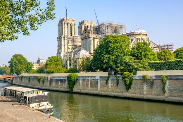 Frankreich paris. sommer sonniger tag. schwimmendes café auf der seine und renovierung von notre dame nach einem brand im hintergrund
