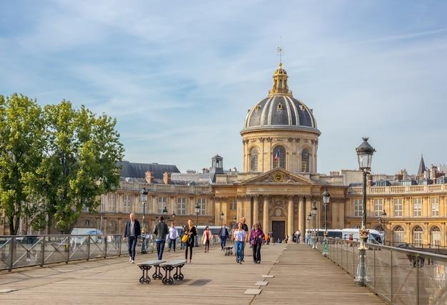 Frankreich. sommertag in paris. menschen auf der fußgängerbrücke der kunst- und mazarine-bibliothek im hintergrund