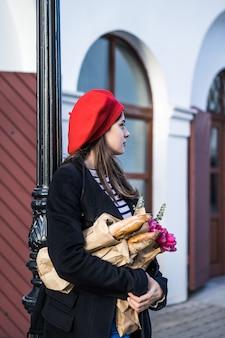 Französin mit baguettes auf der straße im barett