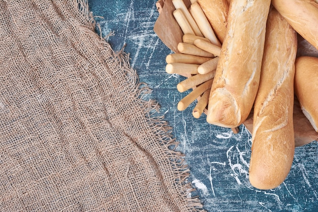 Französische baguettes in einem korb auf blauem tisch.