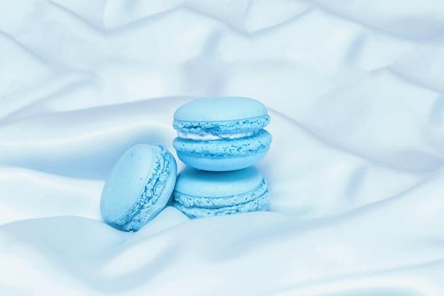 Französische blaue makronenkekse auf seidentischdecke
