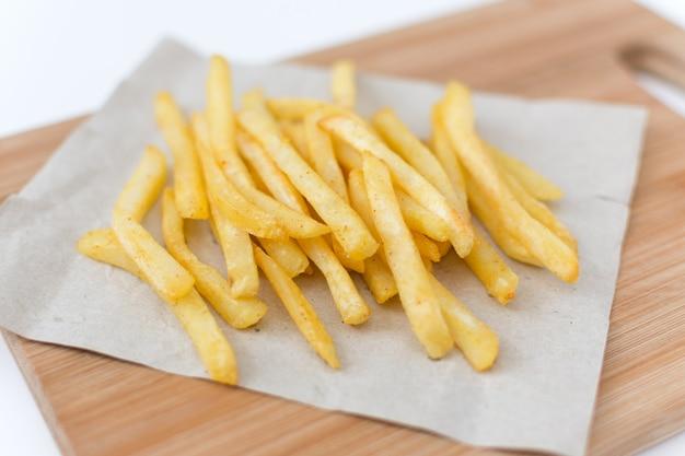Französische bratkartoffeln auf schneidebrett draufsicht.