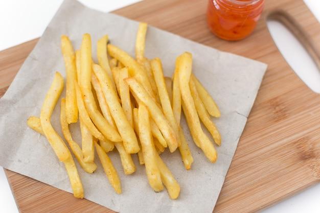 Französische bratkartoffeln auf schneidebrett mit sauce draufsicht.