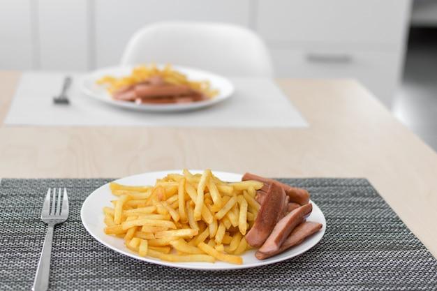 Französische bratkartoffeln mit pommes würstchen auf dem teller. mahlzeit servieren.