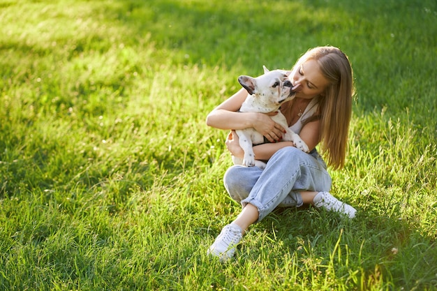 Französische bulldogge, die besitzerin im park küsst