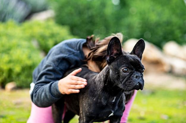 Französische bulldogge, die kleines mädchen in einem park schützt