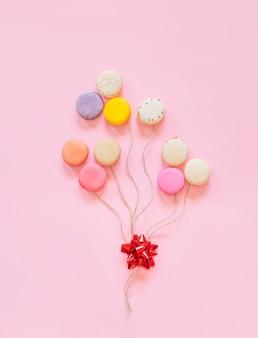 Französische bunte makronen backt in der form von den ballonen zusammen, die auf rosa hintergrund lokalisiert werden.