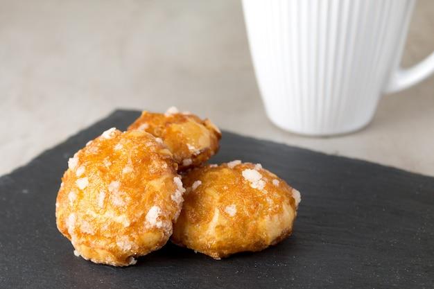 Französische chouquettes puffs mit zuckerperlen auf schwarzem schieferbrett mit weißer tasse kaffee klassische französische bäckereien