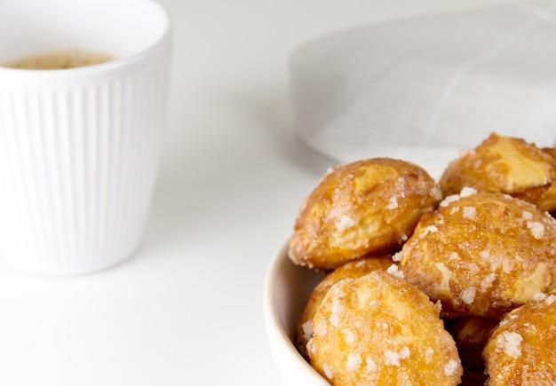 Französische chouquettes puffs mit zuckerperlen auf teller mit weißer tasse kaffee brandteig klassische französische bäckereien