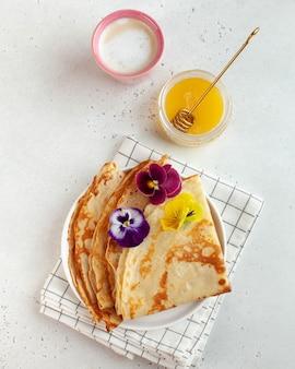 Französische crepes, mit blumen verzierte pfannkuchen, eine tasse cappuccino und honig. konzept des frühstücks, dessert.
