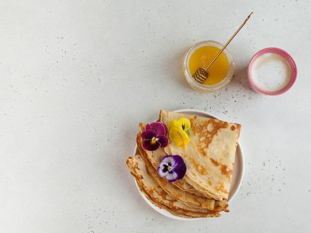 Französische crepes, mit blumen verzierte pfannkuchen, eine tasse cappuccino und honig