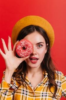 Französische dame in baskenmütze und mit rotem lippenstift, die ihr gesicht mit rosa donut bedeckt.
