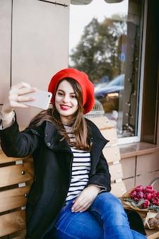 Französische frau in einem roten barett auf einer straßenbank