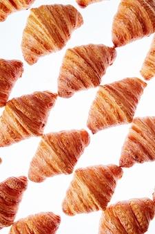 Französische hausgemachte köstliche bäckereien - frische croissants rautenmuster auf einem weißen hintergrund.