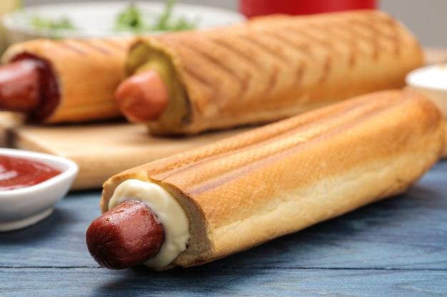 Französische hotdogs. leckere hotdogs auf dem brett und soße auf einem blauen holztisch. fastfood-streetfood. würstchen in einem brötchen.