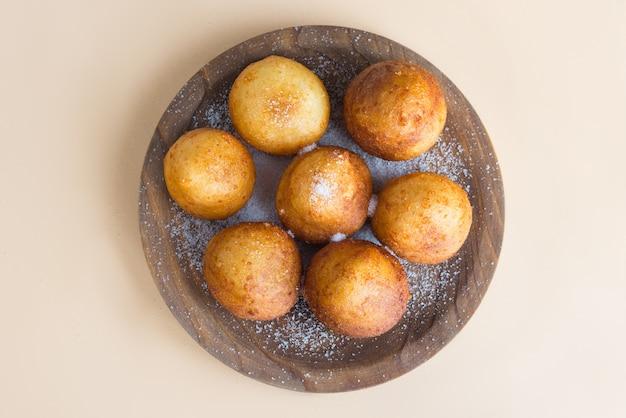 Französische krapfen beignet bedeckt mit zuckerpuder auf einem braun