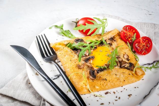 Französische küche frühstück mittagessen snacks veganes essen traditionelles gericht galette sarrasin crepes mit eiern käse gebratene champignons rucola blätter und tomaten