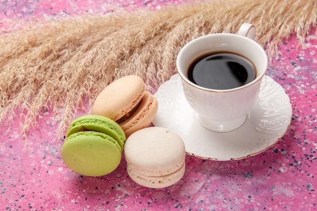 Französische macarons aus der nähe von vorne mit tasse tee auf rosa schreibtischkuchen zucker süße farbe kuchen keks