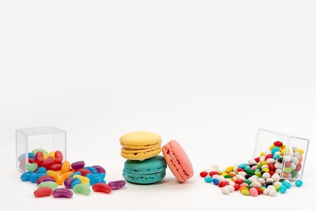 Französische macarons aus der vorderansicht zusammen mit bunten bonbons und marmeladen auf weißem, süßem zucker