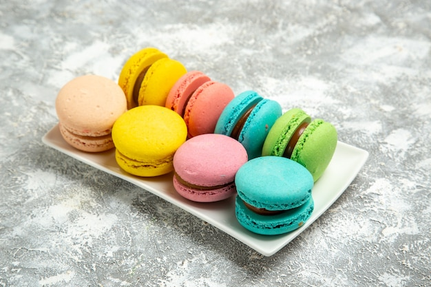 Französische macarons bunte kuchen der vorderansicht auf weißen oberflächenkuchen-tortenzucker-backkeks-süßen keksen