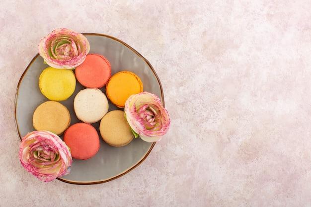 Französische macarons der draufsicht mit blumeninnenplatte auf dem rosa tischkuchen-kekszuckersüß