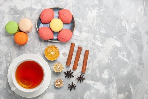 Französische macarons der draufsicht mit kleinen kuchen und einer tasse tee auf weißem schreibtischplätzchenkuchen-kekszucker-süßem tortentee