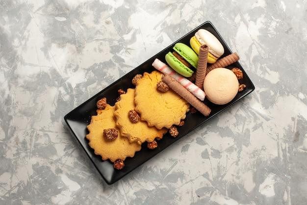Französische macarons der draufsicht mit kuchen und keksen auf süßer torte des kekszuckerkuchens der weißen oberfläche