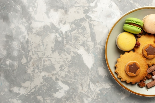 Französische macarons der draufsicht mit kuchen und keksen auf weißem schreibtischplätzchenkekszuckerkuchen süßer torte