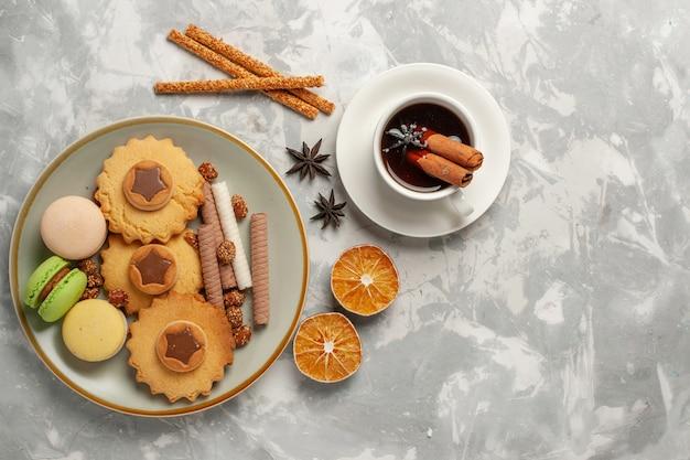 Französische macarons der draufsicht mit kuchen und plätzchen auf der weißen oberfläche plätzchenkekszucker backen kuchen süße torte