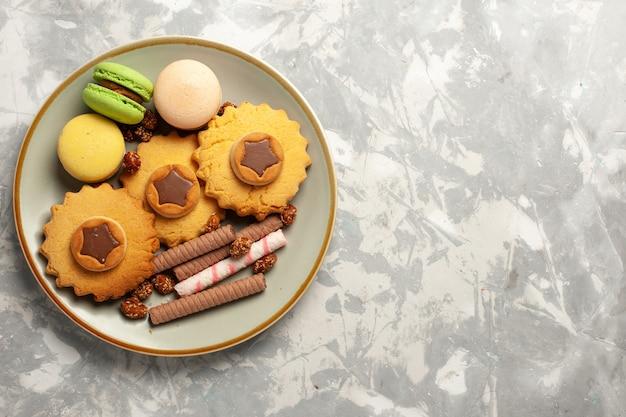 Französische macarons der draufsicht mit kuchen und plätzchen auf kekszuckerkuchen des weißen kekses der weißen oberfläche