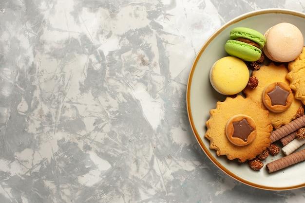 Französische macarons der draufsicht mit kuchen und plätzchen auf süßem tortentee des kekskekszuckerkuchens der weißen oberfläche