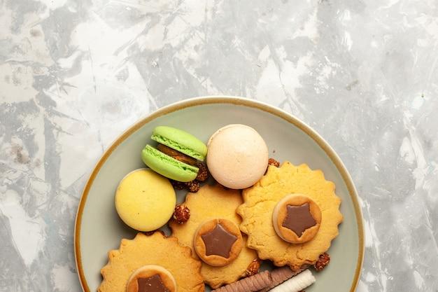 Französische macarons der draufsicht mit kuchen und plätzchen auf süßer torte des weißen kekskekstees des weißen kekses