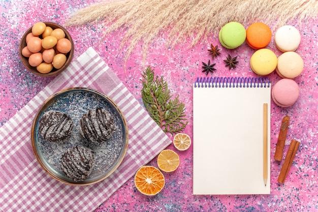 Französische macarons der draufsicht mit schokoladenkuchen auf dem rosa