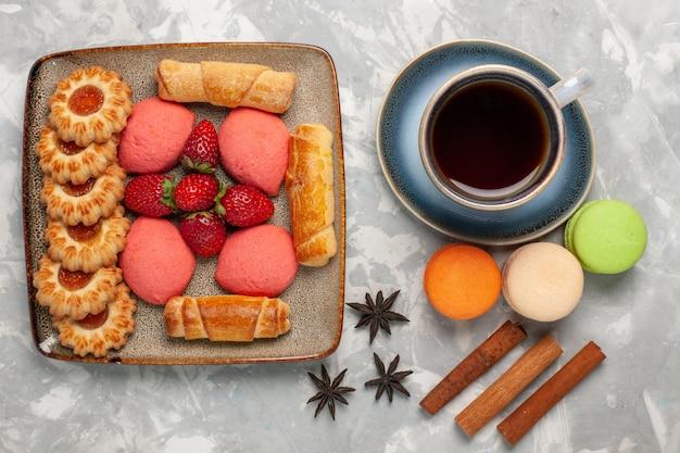 Französische macarons der draufsicht mit tasse teeplätzchen und rosa kuchen auf weißer oberfläche