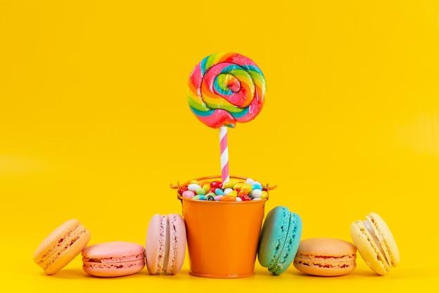 Französische macarons der vorderansicht alogn mit lutschern und bunten bonbons auf gelbem, süßem regenbogen-goody