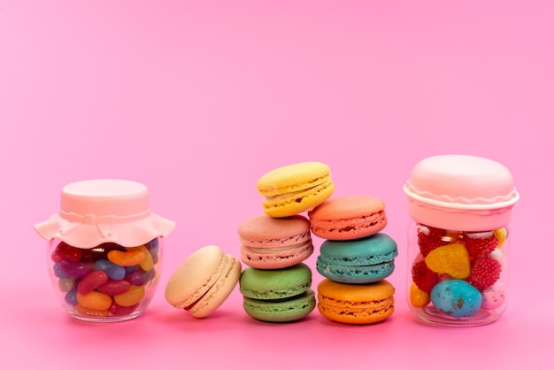 Französische macarons der vorderansicht, die zusammen mit mehrfarbigen bonbons in dosen auf rosa kuchen-keks-süßwaren bunt sind