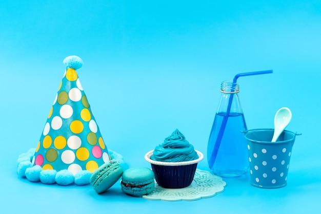 Französische macarons der vorderansicht mit blau, dessertgetränk und geburtstagskappe auf blauem, geburtstagsfeiergeburtstag