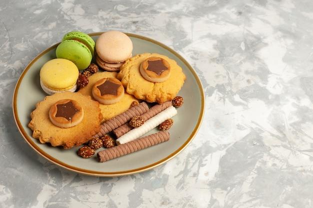 Französische macarons der vorderansicht mit kuchen und keksen auf weißer oberfläche