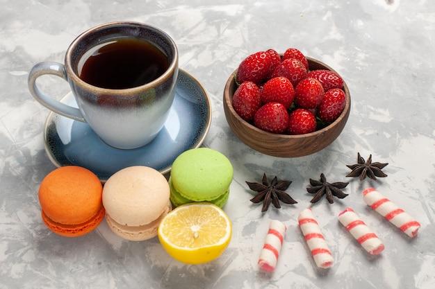 Französische macarons der vorderansicht mit tasse tee auf weißem kekszuckerkuchen des weißen schreibtischkuchens