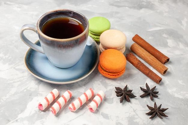 Französische macarons der vorderansicht mit tasse tee auf weißem oberflächenkuchen-kekszuckerkuchen-süßem keks