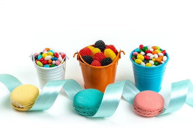 Französische macarons der vorderansicht zusammen mit bunten bonbons und marmeladen auf weißer, süßer kekskuchenfarbe