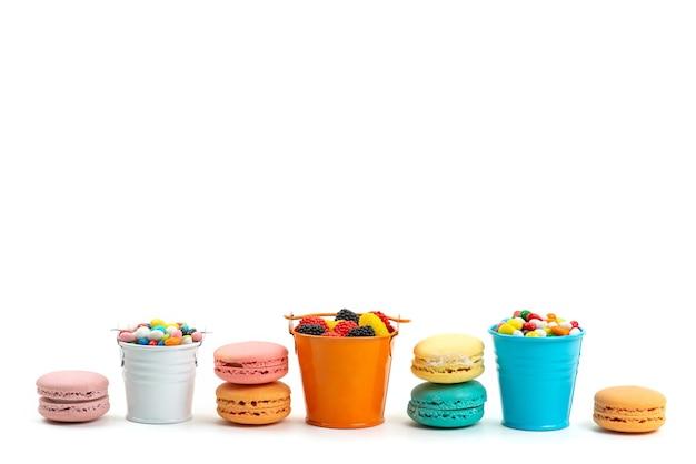Französische macarons der vorderansicht zusammen mit bunten süßigkeiten und marmeladen in bunten körben auf weißer, süßer regenbogenfarbe
