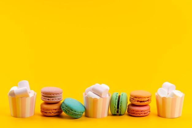Französische macarons der vorderansicht zusammen mit weißen marshmallows, die auf gelben süßwaren der kuchenbonbons isoliert werden