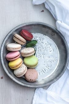 Französische macarons in verschiedenen farben werden auf einer metallischen silberplatte serviert