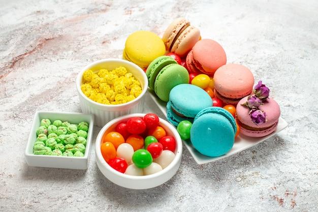 Französische macarons köstliche kleine kuchen der vorderansicht auf weißem raum