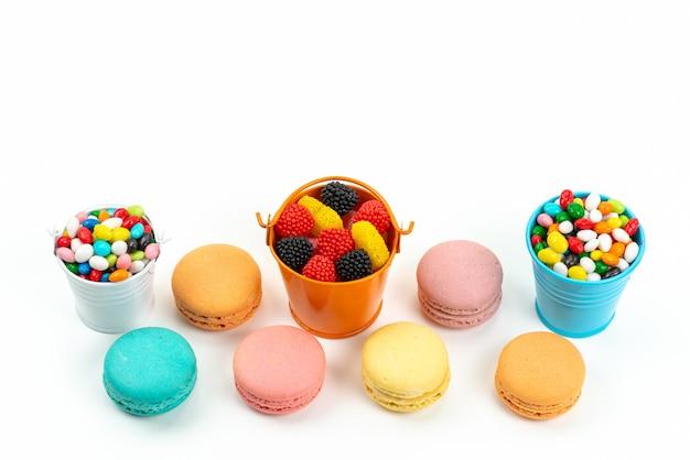 Französische macarons mit draufsicht zusammen mit bunten bonbons und marmeladen auf weißem, farbigem bonbonregenbogen
