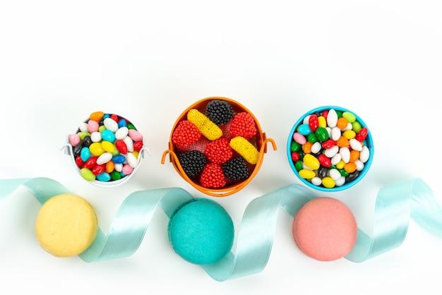 Französische macarons mit draufsicht zusammen mit bunten bonbons und marmeladen auf weißer kuchenkeksfarbe