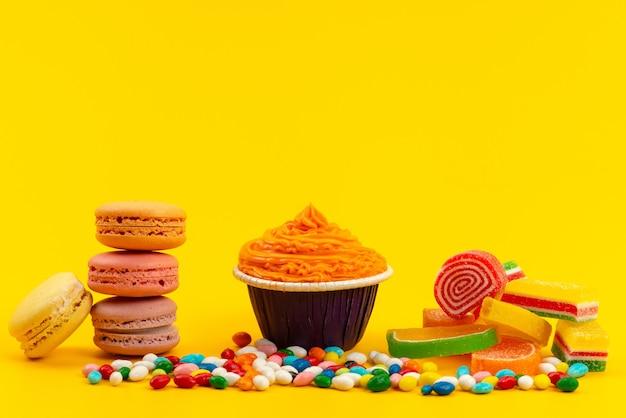 Französische macarons mit vorderansicht, die mit bunten bonbons und marmelade auf gelben süßigkeiten mit kuchenkeksfarbe bekannt sind